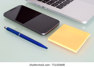Laptop with phone, pen and post it over crystal desktop