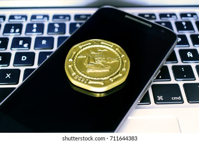 Laptop and phone with pirate coin over screen