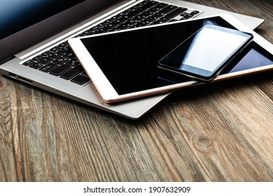 ordinateur portable avec téléphone et tablette sur un bureau en bois
