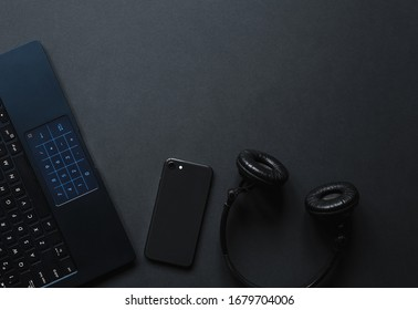 Laptop, phone,  watch,  sunglasses over monochrome black  background. Work accessories of a blogger with copy space and top view. Minimalist black  trendy, Flat Lay