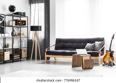 Laptop placed on a modern table standing by the black sofa in man living room interior with window