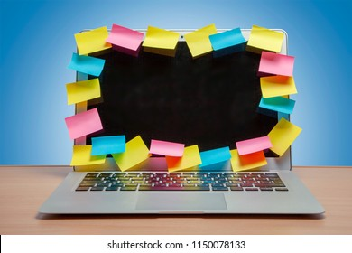 Laptop in reminders with colored stickers notes on the display frame on table with blue wall. Many unfulfilled tasks, deadline