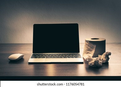 laptop with roll tissue paper on table in the darkroom, mockup for adult video , picture website
