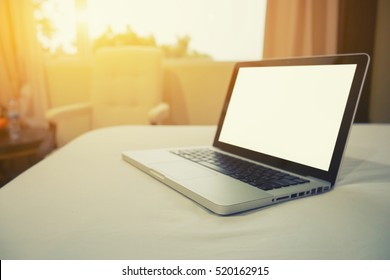 laptop screen on the bed hotel, a blanket lying around it.selective focus,vintage color,morning light