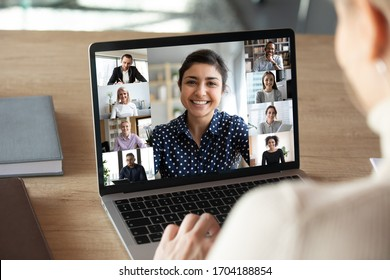 Laptop screen over woman shoulder view, indian businesswoman leading videoconference distant communication group videocall conversation. Diverse friends using modern tech enjoy virtual meeting concept
