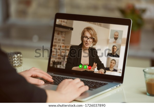 A laptop screen view over a woman's shoulder. A girl listening as a boss gives a task on an online briefing on a computer in her studio. A student listening to a female professor in an online lecture.