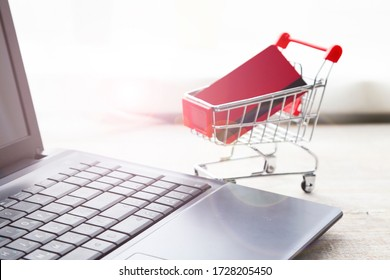Laptop and shopping cart with a credit card. Online shopping.
