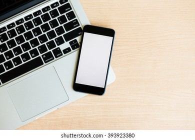laptop with smart phone on table