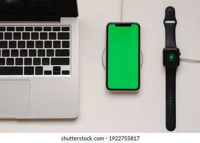 Laptop with smart watch and phone charging on wireless charger. Green screen on phone, on-screen charging indicator on watch. Top view. Place for text