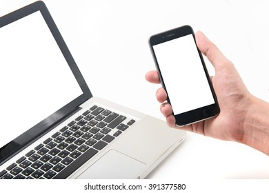 Laptop and smartphone mockup. Closeup of man holding in hand.