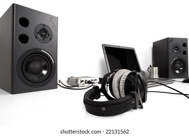 laptop and speakers with headphones on a desk