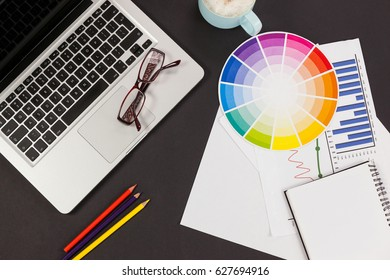 Laptop, spectacles, color pencils, color scheme chart, coffee cup, business graph and diary on grey background