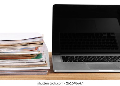 Laptop and stack of magazines on table on white background