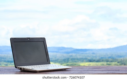 Laptop stands on a wooden table outdoors and nature background