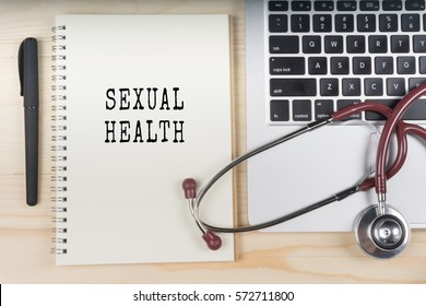 Laptop, stethoscope and notebook on wooden table with SEXUAL HEALTH word as medical concept.
