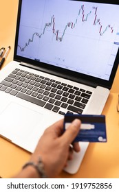 laptop with stock market trading graphic and a hand holding a credit card ready to be used in new investments
