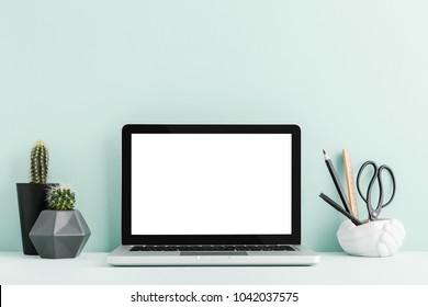 Laptop, supplies cactus on a student desk. Cyan pastel color mock up.