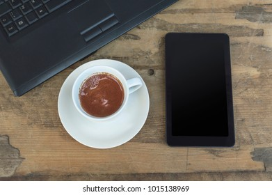 Laptop, tablet and coffee cup on old wooden table, top view