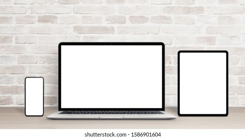 Laptop, tablet and phone mockup on work desk. Modern devices with thin, round edges. Isolated screens for app or web site presentation. Brick wall in background