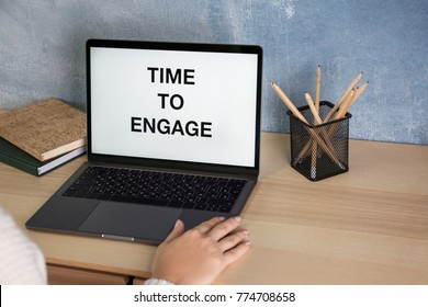 Laptop with text TIME TO ENGAGE on screen and woman at table