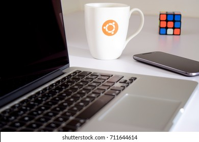 Laptop with Ubuntu coffee mug, rubik's cube and phone