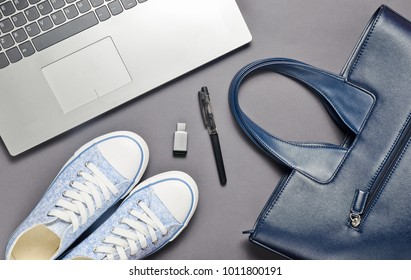 Laptop, usb flash drive and fashionable female accessories on a gray background: bag, wallet, sneakers, bag. Top view. Flat lay.