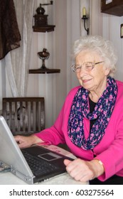Laptop used by smart friendly old woman