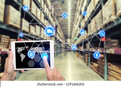 Laptop with white blank screen with global map on brown wooden desk and blurred warehouse store background. Use for cargo Import, Export, Logistics background