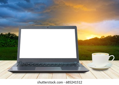 Laptop with white screen and a cup of coffee on wooden table in the forest in the evening