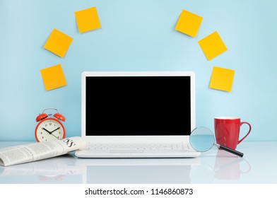 Laptop with yellow blank sticky note and alarm clock on table on blue background. mock up