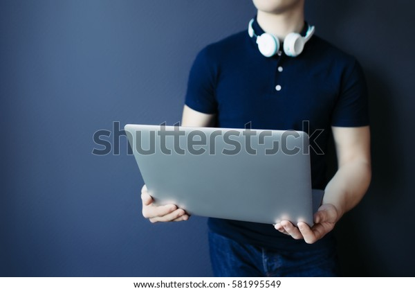 Laptop in young athletic man's hands in t-shirt with headphones.