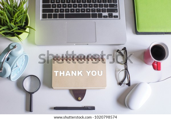 Laptop,magnifying glass,spectacle,pen,coffee,green plant and notebook written with text THANK YOU on white office table.Creative office table lay out view from top.Flat Lay Shot.
