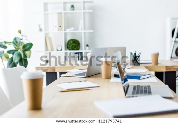 laptops and coffee in paper cups on table in start up office