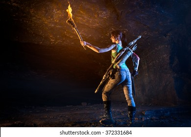 Lara Croft-like character exploring caves holding torch in one hand and knife in the other hand. Wears a bow and arrows on her back.