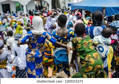 Larabanga, Ghana. September the 19th 2018. Girls observing the crowd at Fire Festival (Bugum Chugu), bringing out the Quran in front of Larabanga Mosque.