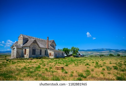 Laramie, Wyoming / USA - July 17, 2013: A deserted gray wooden house on an abandoned ranch on a lonely road in Wyoming.