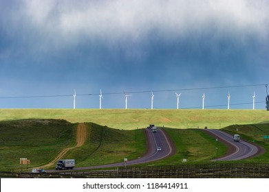 Laramie,Wyoming,USA - June 1, 2018:  Wind turbines line the hill under stormy skies as traffic travel  on east and west bound lanes of Interstate 180 through Wyoming, USA