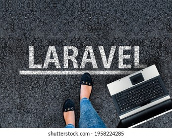 Laravel PHP Framework programming language. Woman legs in sneakers standing next to laptop and word Laravel