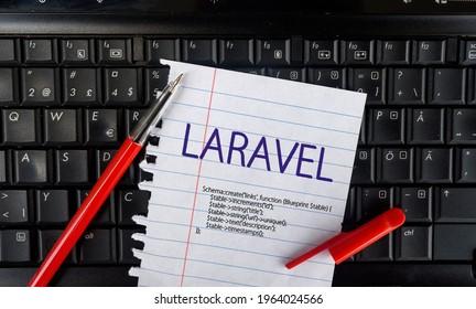 Laravel PHP Framework programming language. Word Laravel on paper and laptop