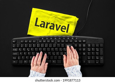 Laravel PHP Framework programming language. Laravel word on rag and hands on pc keyboard