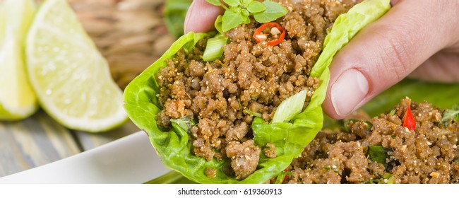 Larb - Lao minced beef salad with fish sauce, lime juice, roasted ground rice and fresh herbs served with lettuce leaves for wraps.