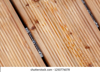 Larch decking fragment mounted with oval decking connector. Simple connection of wooden decking boards without a visible screwed joint in wood board.