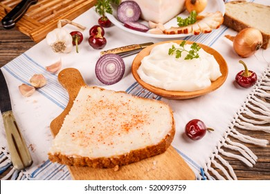 Lard bread with red paprika on rustic table