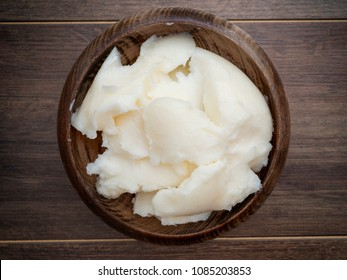 Lard or pig fat in wooden bowl on dark background directly above