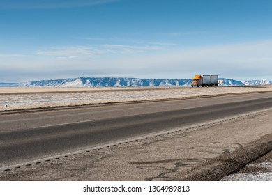 Large, 18-wheeler truck dirves through the western American state of Wyoming with a scenic, wintry Rocky Mountain landscape as background.