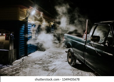 A large 4x4 truck idling near a building on a cold winter night.