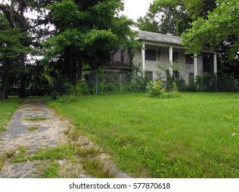 Large abandoned building on the right with an overgrown driveway on the left.