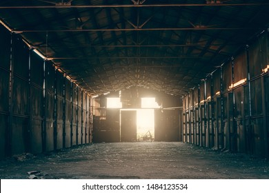 Large abandoned empty and dirty rusty iron hangar, creepy warehouse inside, toned