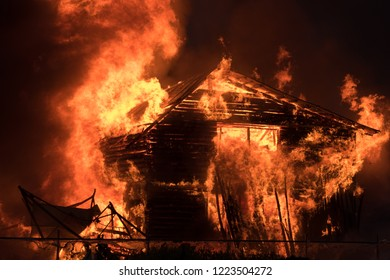 A large abandoned one-story wooden house ignited and burned. The structure of the log. High powerful fire above the roof. Dangerous situation for the forest and nearby buildings. Increased fire hazard
