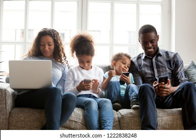 Large African American family using mobile devices, sitting together at home, preschooler daughter, toddler son using phones, mother shopping with laptop, father with smartphone, addicted with devices